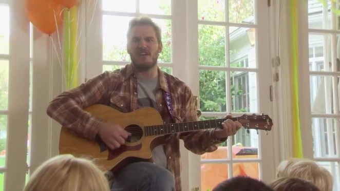 Flannel-wearing Andy plays guitar at a kids' party