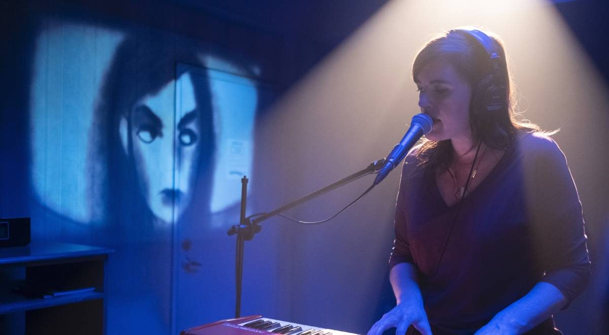 Nina plays the keyboard as an animated girl is projected on the wall behind her