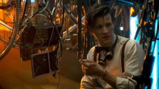 The Doctor, wearing goggles around his neck, tinkers with the workings of the TARDIS