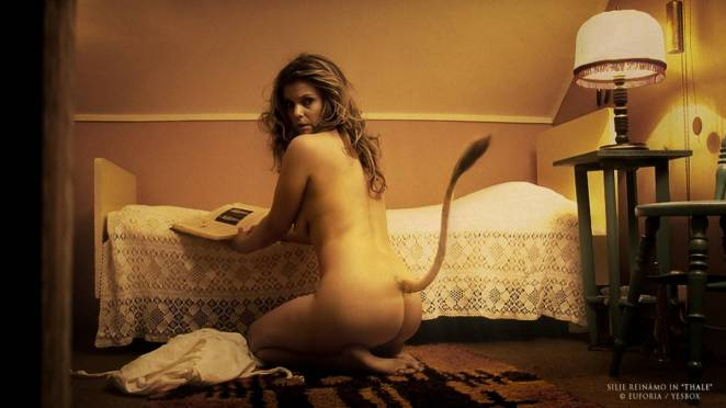 A naked woman with a cows tale looks over her shoulder while kneeling beside a bed and looking at a book in Thale