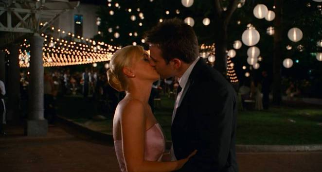 Ally and Colin kiss with a wedding reception in the background