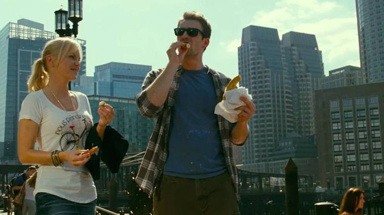 Colin eats a pretzel while walking with Ally through a park with the city of Boston in the background