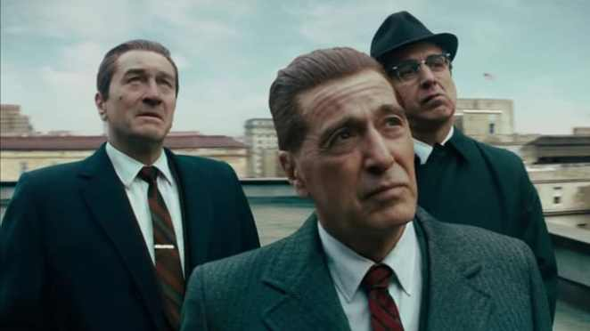 Three men examine something in the air in The Irishman