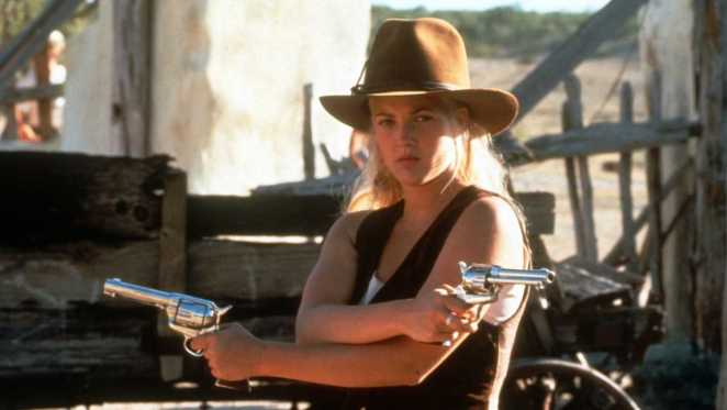 Lily points two guns in opposite directions with her arms crossed.