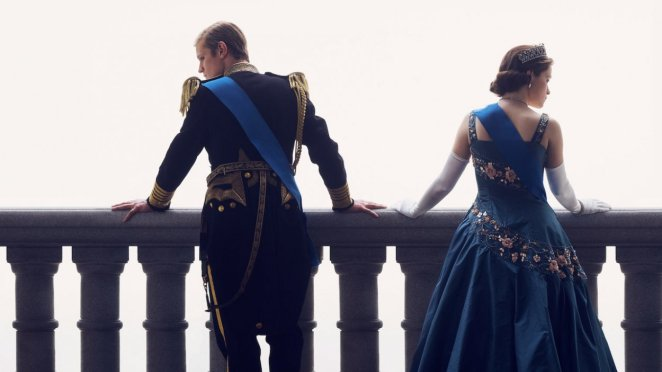 Philip and Elizabeth stand on the palace balcony looking in opposite directions while dressed in Royal clothing