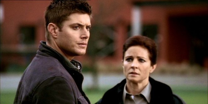 Dean staring at something off to the right with Sheriff Kathleen staring at him in concern