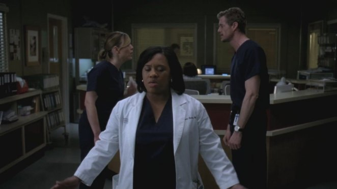 Bailey (Chandra Wilson) leaves Arizona (Jessica Capshaw) and Mark (Eric Dane) to help Lori. Bailey stands in the foreground with her eyes closed, while the other two face off behind her and seem to be arguing.