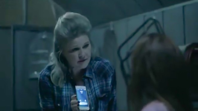 Alma holds a ringing cell phone up to Marjorie