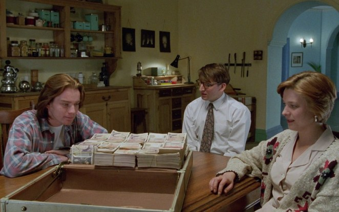 Ewan McGregor, Christopher Eccleston, and Kerry Fox sit at a table with a briefcase full of money