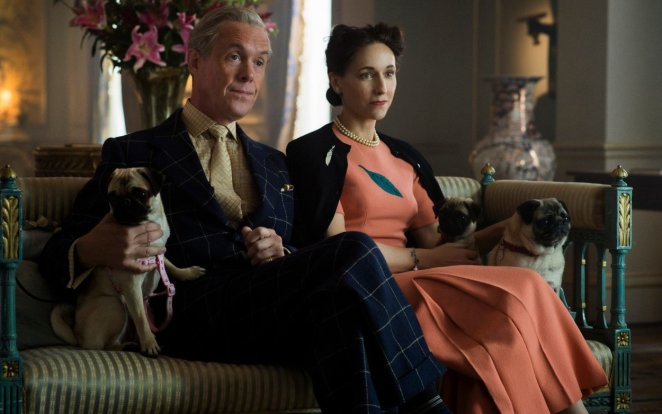 Edward VIII and Wallis Simpson sit on a sofa with their dog, dressed in formal outfits while giving an interview