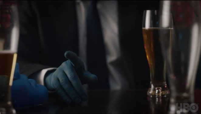 Watchmen - A blue hand belonging to a man in a black suit