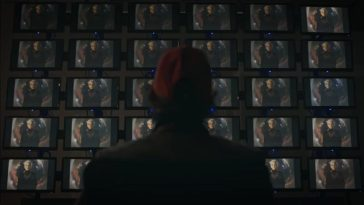 Watchmen - Wade stands facing dozens of screens featuring a young Adrian Veidt