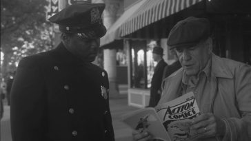 Watchmen - Officer Reeves and the newsstand guy look through a copy of Action Comics No. 1