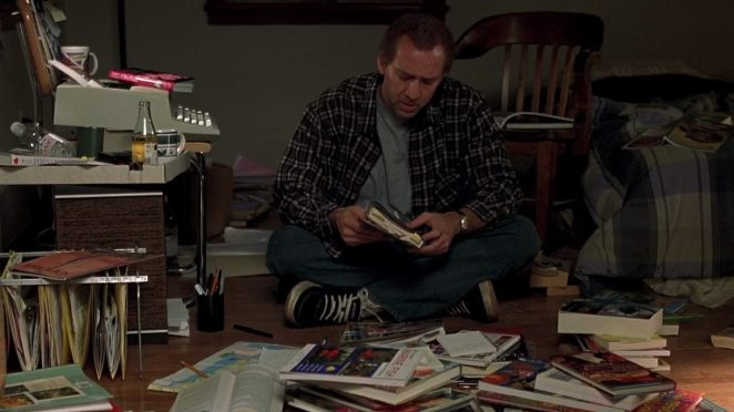 Charlie played by Nicolas Cage looks through books for inspiration
