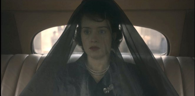 Elizabeth rides in the back of a car while wearing a long black veil