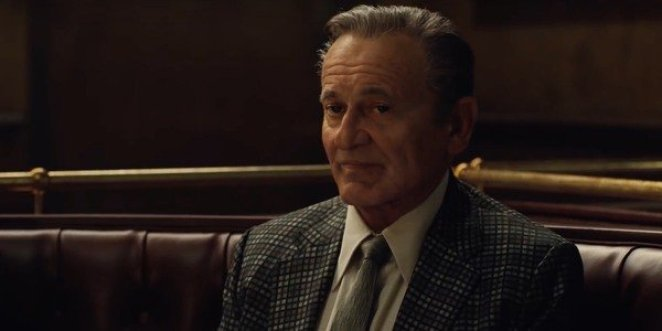 Joe Pesci as Russel Bufalino sits listening in a restaurant booth in The Irishman