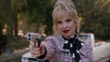 Margaret points a gun while wearing stylish clothes and looking smug
