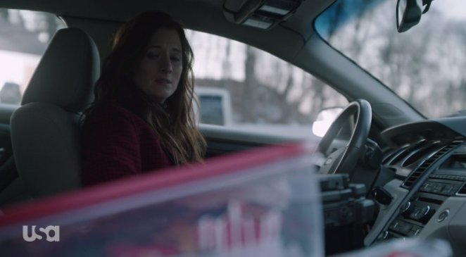 Dom looks pained as she looks at her tupperware of Christmas cookies in her car
