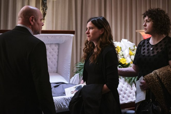 George yells at Eve in front of Roy's coffin as Amanda watches