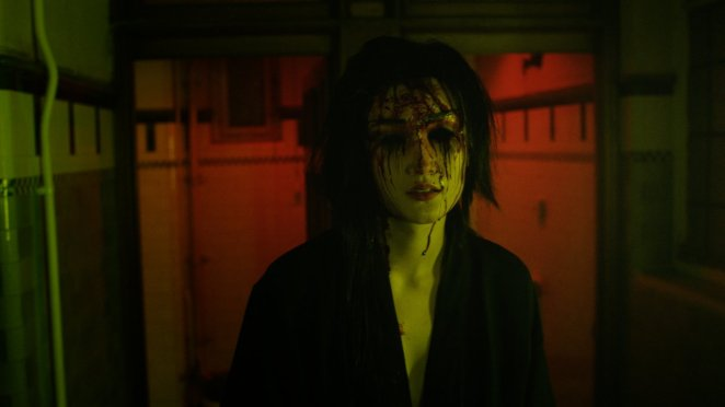 A woman with dark hair and black eyes, with blood streaming down her face stands in a dimly lit room