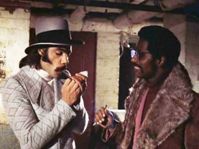 Priest (Ron O'Neal) and Eddie ( Carl Lee) are stood in an alleyway having a conversation. Priest is lighting a cigar as Eddie looks on, smiling, in Superfly