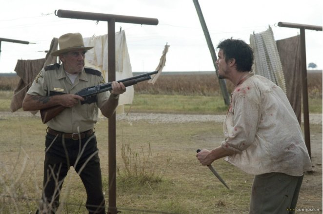 R. Lee Emery's character points a shotgun at one of the other characters, who is yelling and wielding a knife