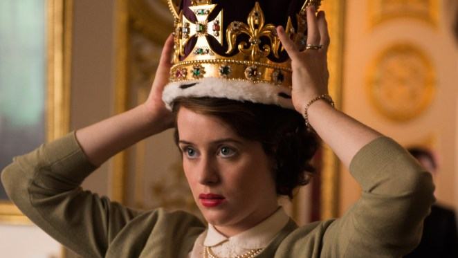 Elizabeth tries on the crown while looking nervous and wearing a green cardigan