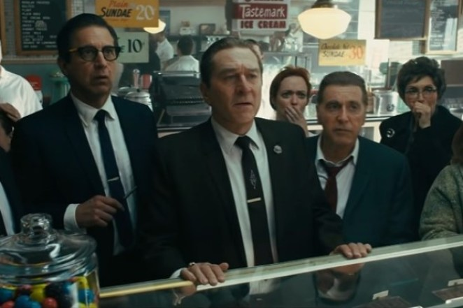 Three men in suits look at a TV at a store counter while two women appear shocked