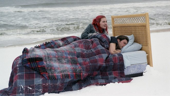 Clementine and Joel lie in bed on a snowy beach