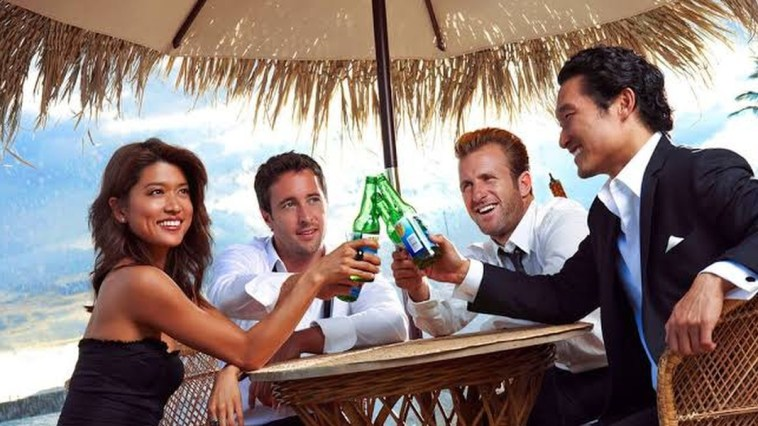 Kono, Steve, Danny and Chin sitting at a table, clinking their glasses together in Hawaii Five-0