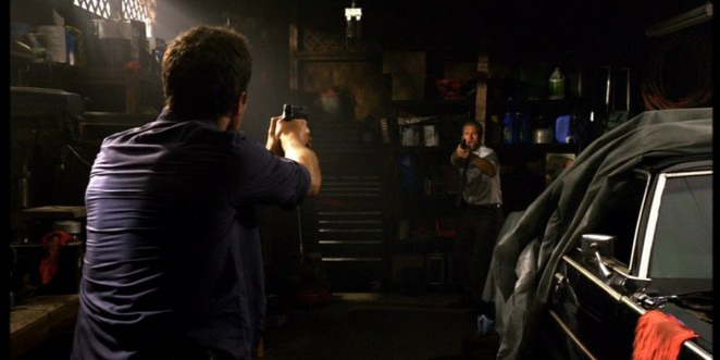 Steve has his back to the camera while pointing his gun at Danny who is also pointing a gun at Steve as they face each other in a garage