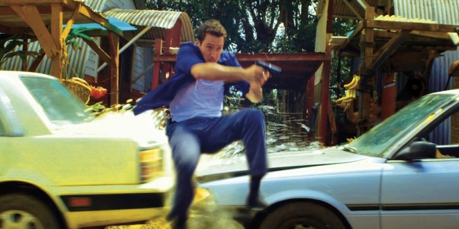 Steve leaping in the air holding a gun as two cars collide behind him Hawaii Five-0