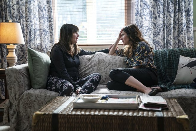 Eve and Jane sit opposite each other on the couch as Eve consoles Jane