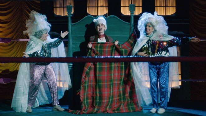 Zoya dresses as Scrooge, in bed in the boxing ring