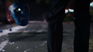 Dr. Manhattan shot from the knees down is shown from behind holding a mask of his likeness.