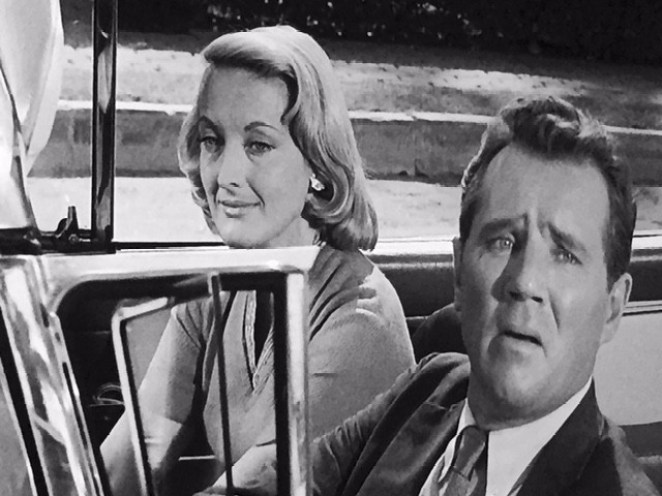 """Arthur/Gerry looks confused in his car with his """"wife"""" Nora"""