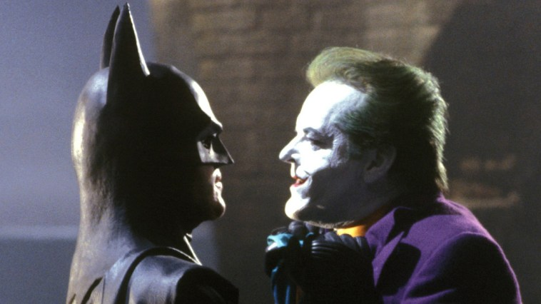 Batman holds Joker close to his face by the scruff of his neck