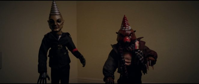 Two evil dolls with cone heads stare at the camera.