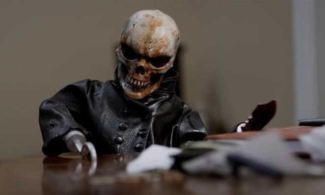 Evil doll, Skull Blade, leans over a table and puts his hook hand on it.