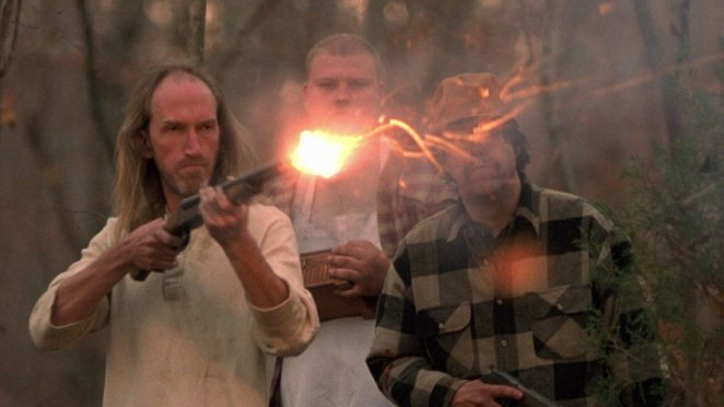 Three local men stand, each armed, while one, a balding man with long hair, fires a double barreled shotgun.