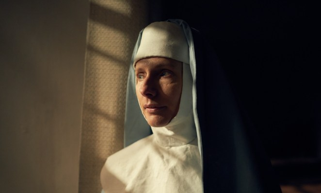 Dolly Wells as Van Helsing wearing a nun's habit and looking out the window