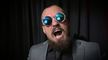 Marty Scurll poses against a black curtain in his suit and sunglasses