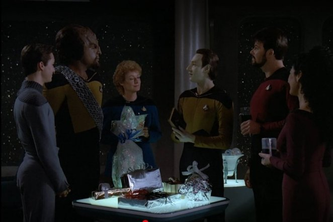 Data opens a gift with the crew