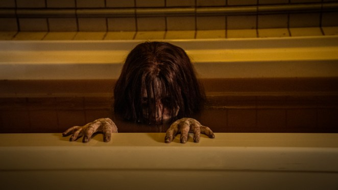 A ghost of a young girl peering her head above the water in a bath