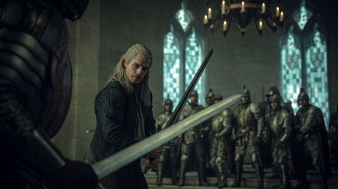 Geralt (Henry Cavill) raises his sword against the guards in a court.