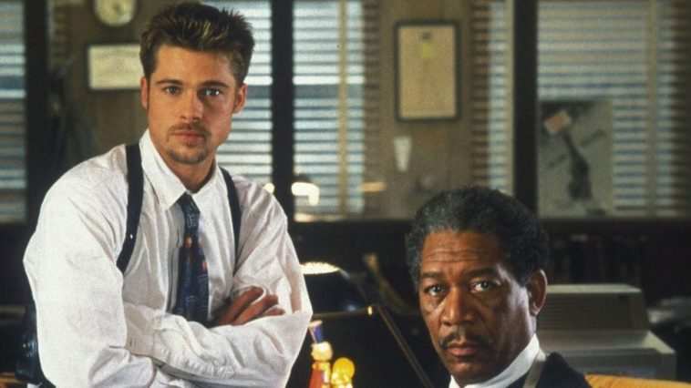 Brad Pitt and Morgan Freeman as detectives sit around a desk in Seven
