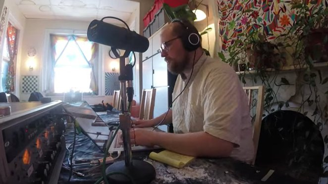 Dan Deacon hard at work in his studio with headphones and a laptop