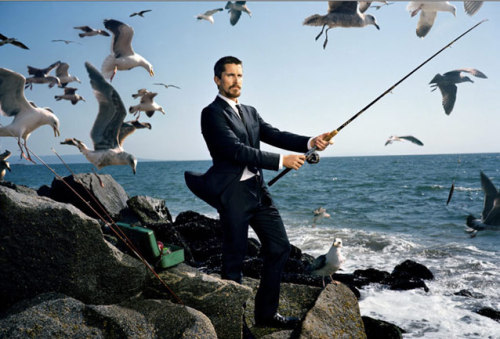 Christian Bale standing on rocks by the sea wearing a designer suit.  He is holding a fishing rod and is surrounded by seagulls.