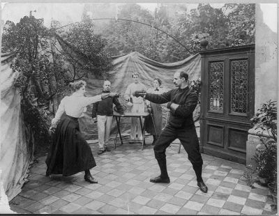 Edwardian postcard showing a man and woman fencing