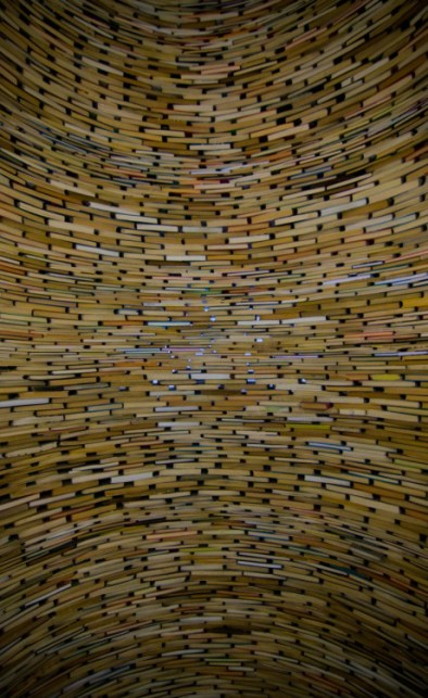Image - photo of a curved wall made out of BOOKS stacked like bricks. There would have to be hundreds and hundreds of books in this wall! Or… maybe they're built on a mirror? There is some distortion on the top and bottom of the photo. TIMES WHEN I SUCK AT DESCRIBING PHOTOS!